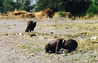 Di Afrika. Seekor burung pemakan bangkai sedang menunggu seorang bocah yang sedang sekarat kelaparan