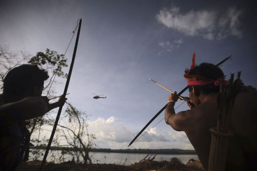 Indigenous people point their bows and arrows at a police helicopter flying over the occupied barrier of the Belo Monte Dam's construction site in Vitoria do Xingu, near Altamira