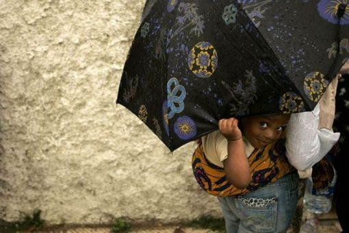 A child peeps from under an umbrella during a protest in Rabat